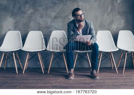 Close Up Of Concentrated Pensive Bearded Guy In Formal Wear And Glasses. He Is Sitting In The Hall O