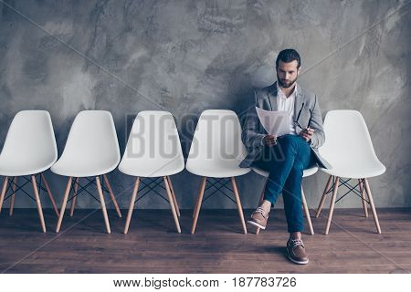 Concentrated Young Bearded Guy In Formal Wear Is Preparing For An Interview, Sitting In The Hall On