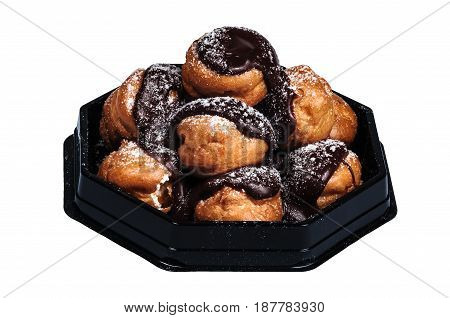 Profiteroles in a heap rich Belgian chocolate white background