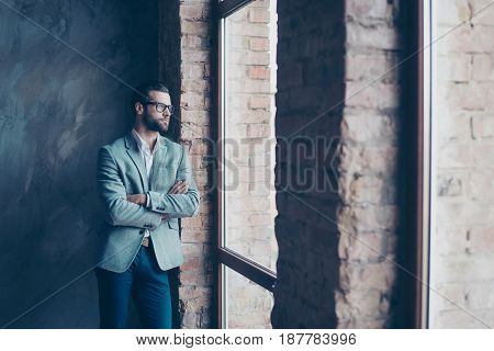 Success Concept. Stylish Young Bearded Man Is Standing Near The Window And Looking Far. He Looks So