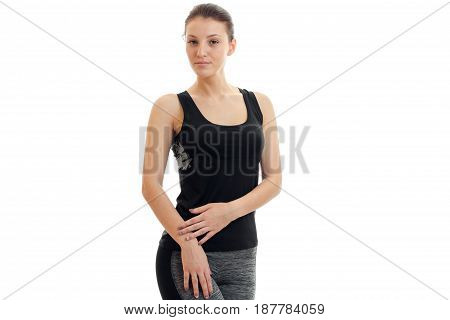 charming young slender girl in grey sports suit looks into the camera and stands isolated on white background