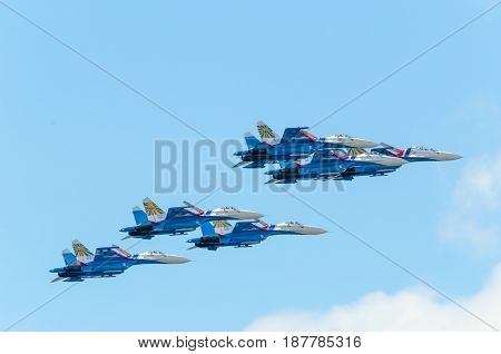 SAINT PETERSBURG, RUSSIA - JULY 5, 2015: six combat supersonic fighter su-27 painted in blue and red colors are flying in a tight group, close to each other as a team, against the blue sky. July 5, 2015.