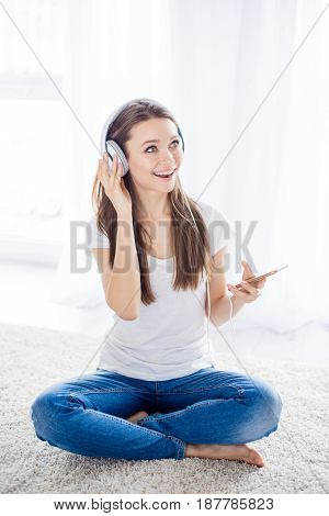Energetic Young Girl Listening To Music In Headphones Sitting On The Floor. She Turned On Her Favori