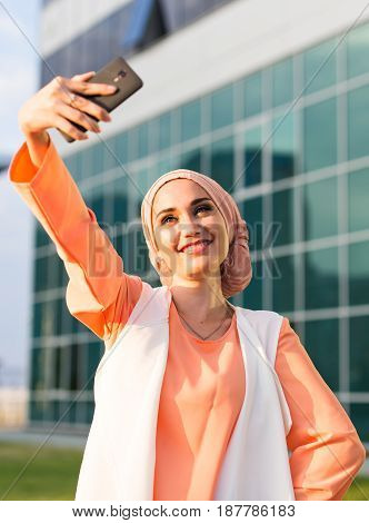 Arabian muslim islamic woman taking selfie outdoors