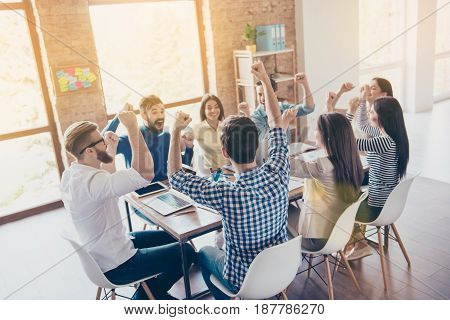 Success And Team Work Concept. Team Of Business Partners With Raised Up Hands In Light Modern Workst