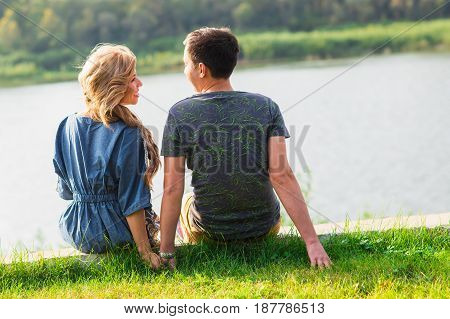 Young love couple sitting on the river bank in summer.