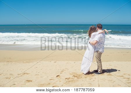 Young romantic couple standing on the beach, looking in the distance, hugging. Rear view