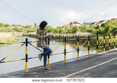 Young Beautiful Woman Standing Next To The Lake  Texting Messages