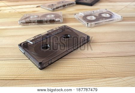 Several sound cassettes lie on a wooden background