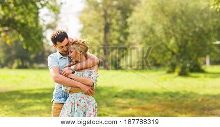 Couple embracing on the countryside. Young romantic man and woman standing and hugging each other with tenderness on nature. Young love concept