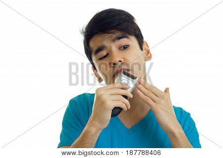 funny young guy with black hair stares into the distance and carefully shaves mustache trimmer is isolated on a white background close-up