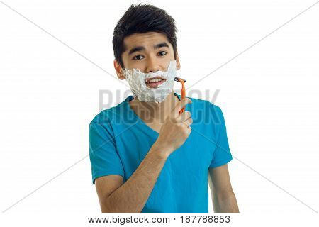 cute young guy in a blue t-shirt and with black hair looks straight and shaves his beard machine with foam on his face isolated on white background.