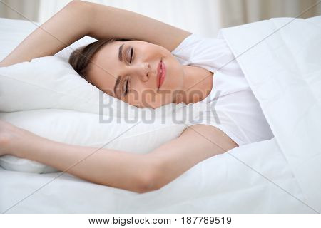 Woman stretching in bed after wake up, entering a day happy and relaxed after good night sleep. Sweet dreams, good morning, new day, weekend, holidays concept.