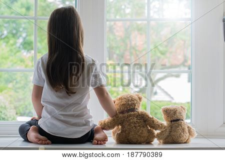 Little Girl On Window With Teddies