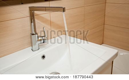 Bathroom faucet with flowing water on white ceramic washbasin