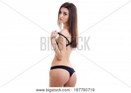 great young brunette in black lingerie worth backwards with sexy round buttocks isolated on white background