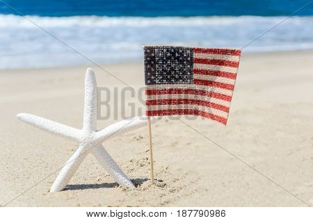 Patriotic USA background with starfish and american flag on the sandy beach
