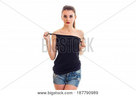 charming pretty girl with red lipstick stands right keeps hand t-shirt on your body and looking at camera isolated on white background