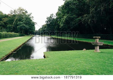 Pond in a formal garden with grass and trees