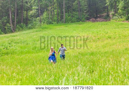Young man and woman running on countryside meadow with green grass.