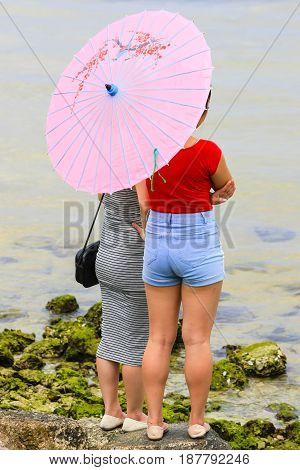 Tampa Bay, FL, USA - 09/05/2016: Two girls standing at the waters edge of Tampa bay holding a paper parasol