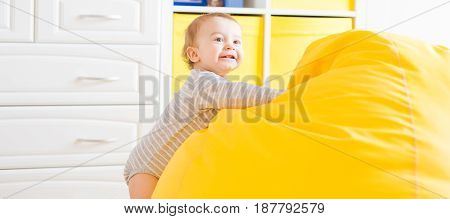 Cute happy laughing baby boy playing on white bedroom