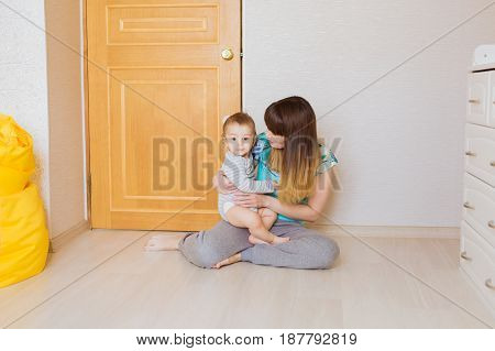 Happy mother with adorable baby boy indoors.