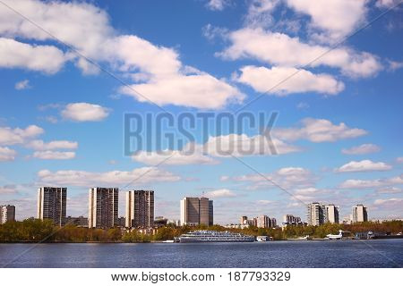 cityscape with spring cloudy sky, houses and river bank photo