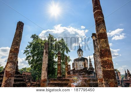 Ancient Buddha statue sitting among the ruins under the bright sun of Wat Maha That temple in Sukhothai Historical Park is an old city and famous tourist attraction of Sukhothai Province Thailand