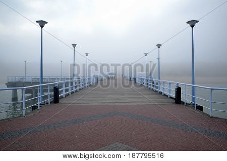 Pier overlooking the misty beach by the sea