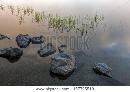 Large rocks shown just above the surce of this calm water in ealry morning.
