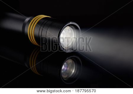 Black metallic LED flashlight with ray light on a black background.