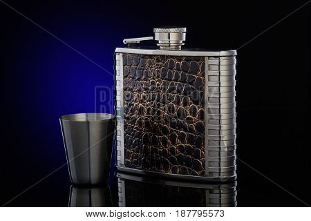 Hip flask from stainless steel with brown leather  for whisky or cognac and steel drinking glass on a dark blue background with copy space.
