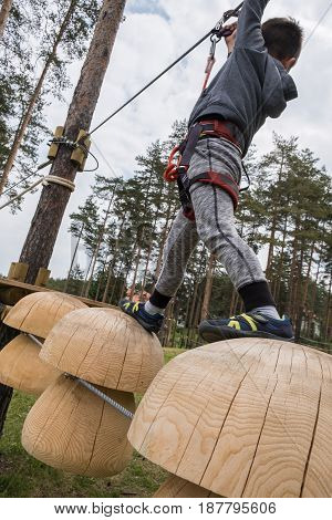 Small boy on obstacle course in outdoor adventure park