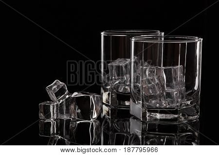 Two glasses for whiskey with ice cubes on black background.
