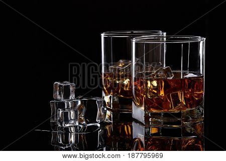 Two glasses of scotch whiskey with ice cubes on a black background.