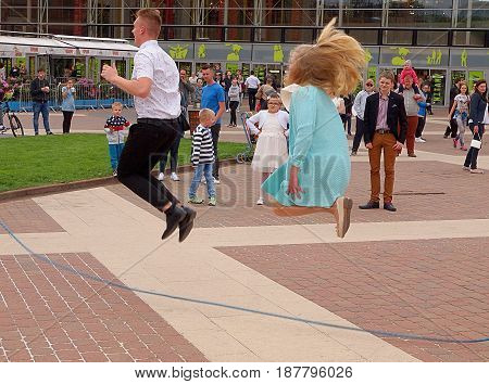 Synchronized jump. Lodz, Poland - May 21, 2017 Woman and man during the jump through the scan at the Bicycle Festival in Lodz.