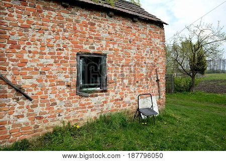 Tary rural building in the wilderness and lonely chair