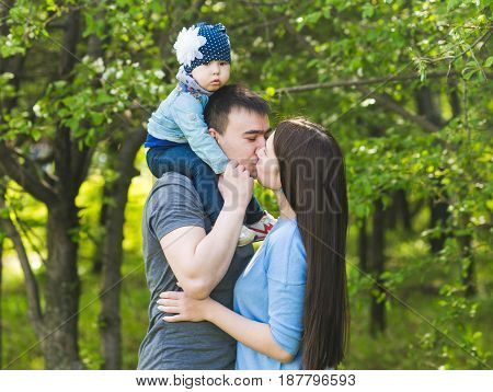 Family spending time together in the park in spring time. Mother, toddler and father playing in blooming garden