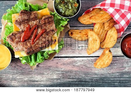 Canada Day Picnic Scene With Maple Leaf Shaped Hamburger And Potato Wedges Over Dark Rustic Wood