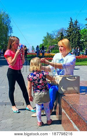 mother corrects her daughter's hair during a walk through the spring town. Family walk through the spring town