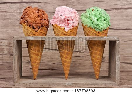 Chocolate, Cherry And Pistachio Ice Cream In Waffle Cones In Rustic Holder Over A Wood Background