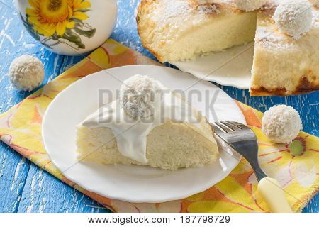 Cottage cheese casserole with coconut. Decorated with curd balls in coconut shavings. Delicious and healthy breakfast. Served with yoghurt sauce
