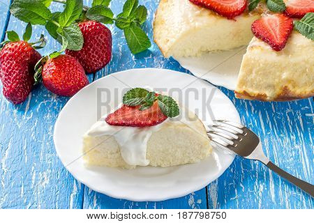Cottage cheese casserole with coconut shavings. It is decorated with fresh strawberries and mint. Delicious and healthy breakfast. Served with yoghurt sauce