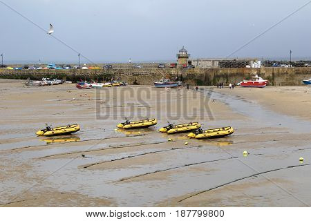 St Ives Cornwall UK - April 2 2017: Dinghies belonging to St Ives Self Drive Boats and other trawlers and small yachts in St Ives harbour at low tide