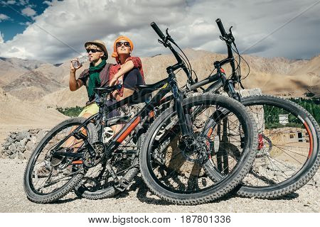 Two cyclists rest n the mountain road