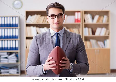 Businessman with american football in office