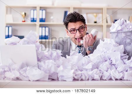 Businessman in paper recycling concept in office