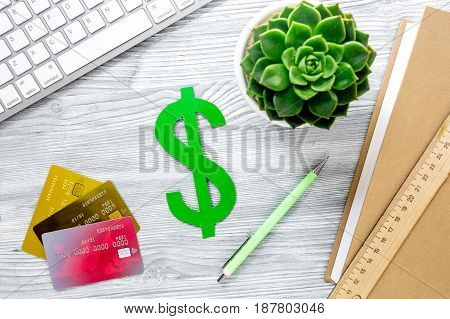 fee-paying education set with dollar sign, books and creit cards on light wooden table background top view