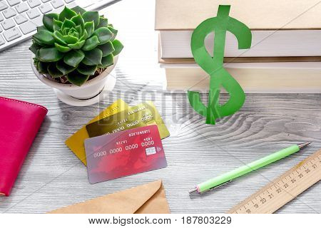 paying for studing concept with dollar sign and credit cards on light table background